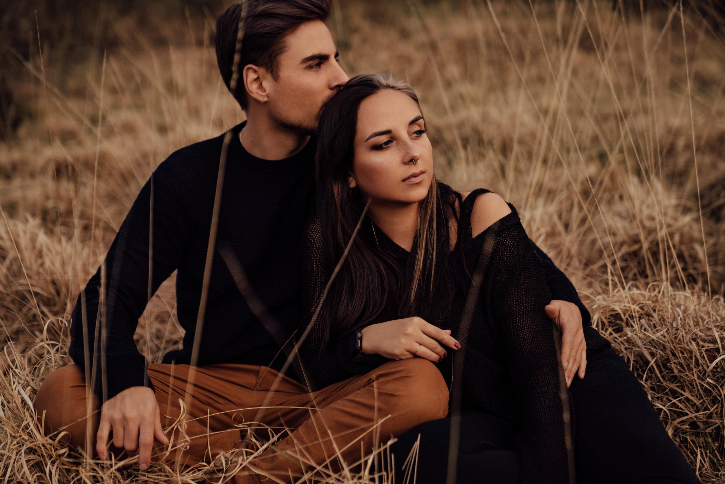Pärchen sitzt aneinander gekuschelt in trockenem Gras und schaut gemeinsam in die Ferne. Portrait von zwei Fotografen.