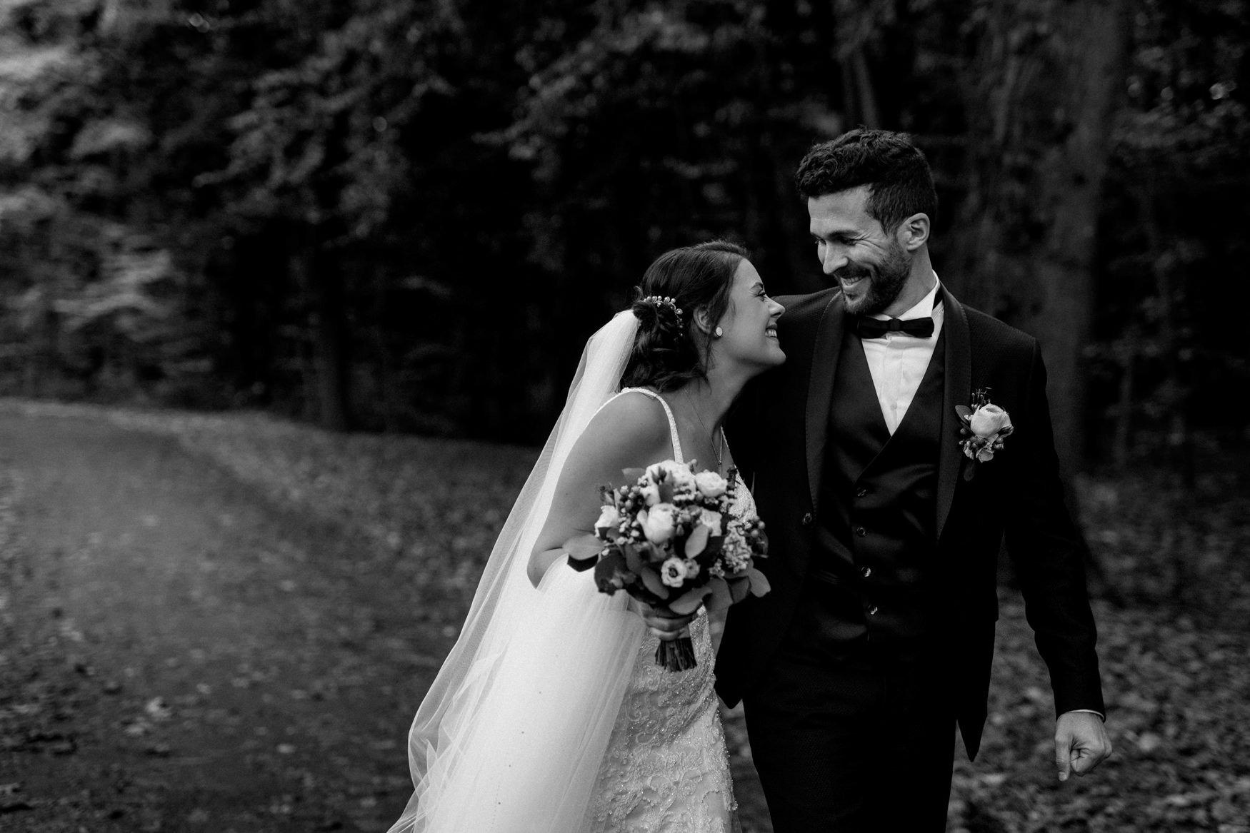 lachendes, glückliches Brautpaar läuft Arm in Arm durch einen Herbstwald