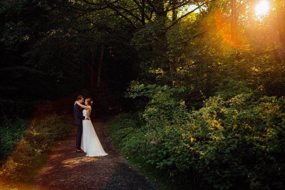 Brautpaar am Waldrand mit schönen Sonnenstrahlen.