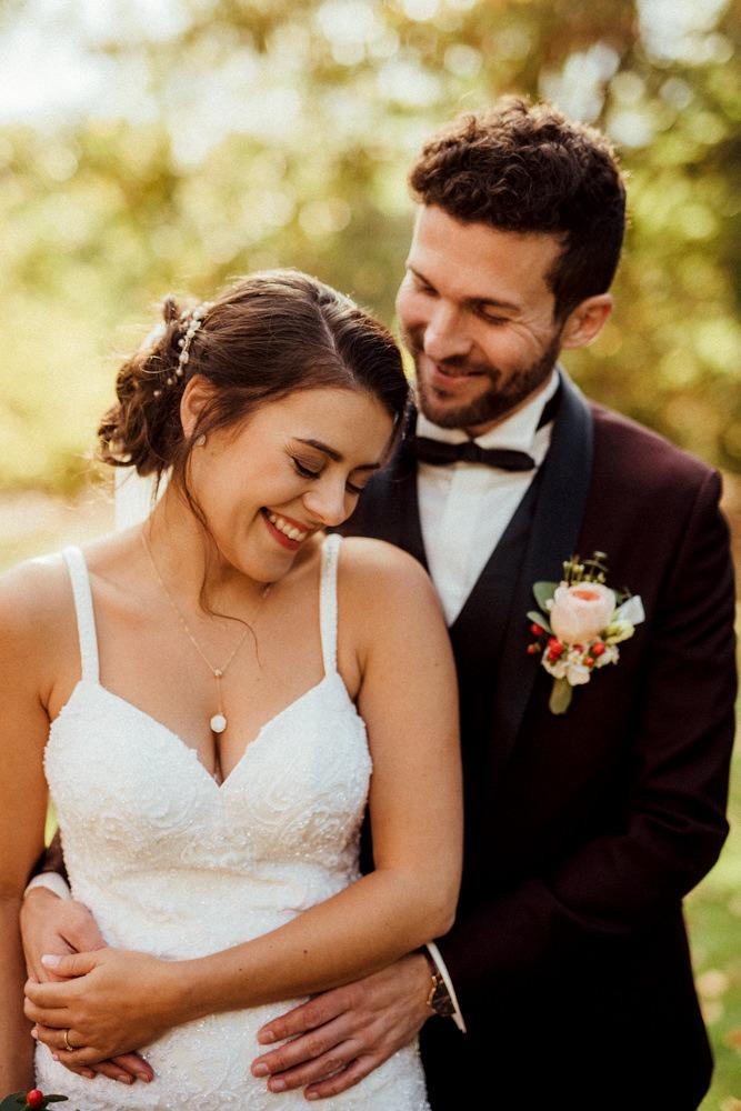 Bräutigam umarmt Braut von hinten im Sonnenschein. Sie strahlen über beide Ohren.