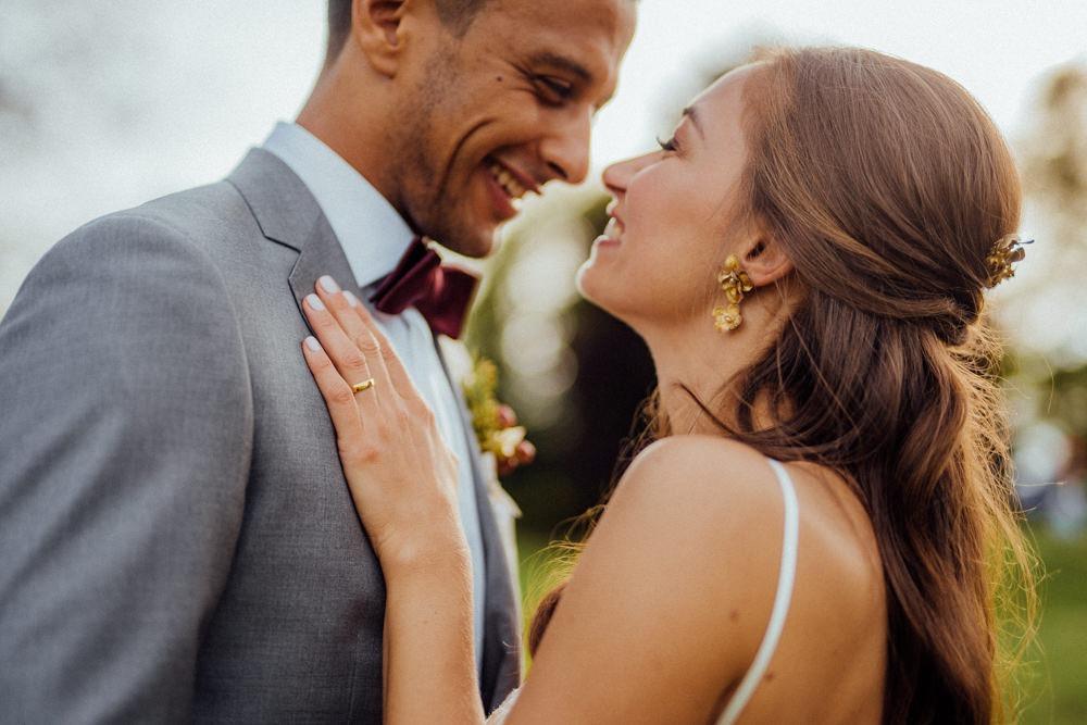 Braut lacht ihren Bräutigam an. Beide genießen ihren Hochzeitstag.