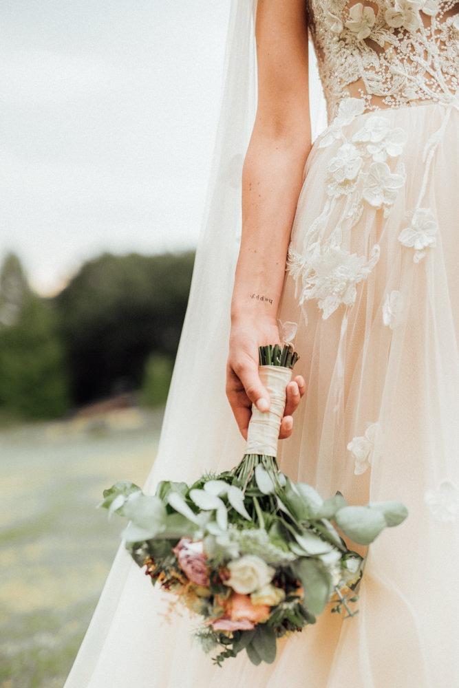 Detailshot von einem wunderschön verzierten Hochzeitskleid und einem Brautstrauß in Pastelltönen. Tätowierte Braut mit zierlichem Schriftzug am Handgelenk.