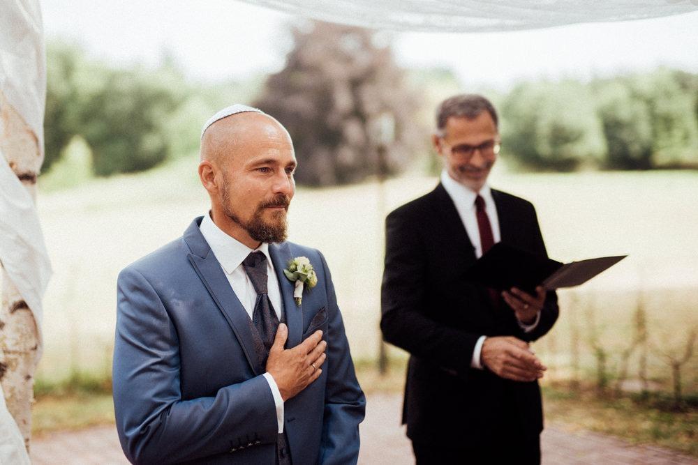Jüdische Hochzeit mit freier Trauung. Bräutigam fasst sich ergriffen an sein Herz, als er seine Braut das erste Mal sieht. Er ist den Tränen nahe.