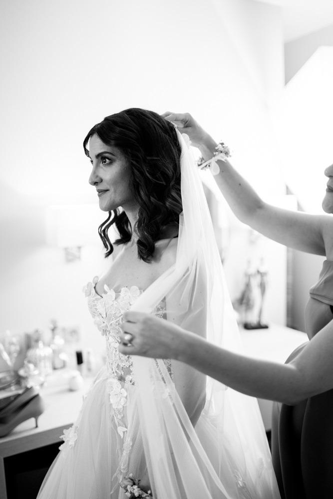 Getting Ready. Schwester der Braut legt ihr ihr den Schleier an. Während beide für den letzten Schliff nochmal in den Spiegel schauen.