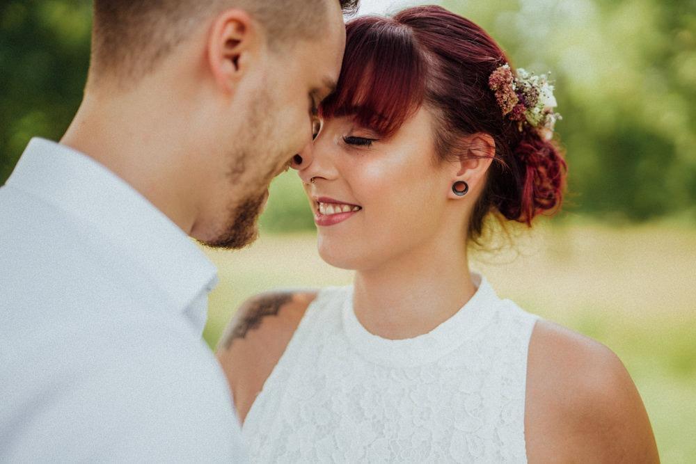 Junge Braut mit knallroten Haaren und Blumen in ihrer Steckfrisur kuschelt sich an ihren Bräutigam. Sommerhochzeit ganz in weiß.