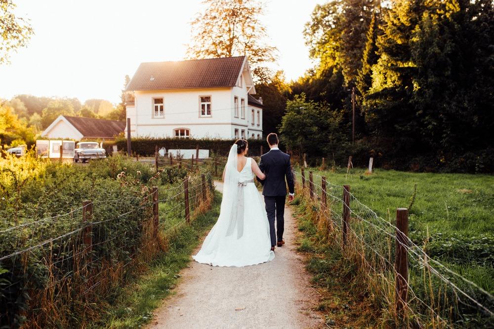 Brautpaar läuft Arm in Arm an einem Feldweg vorbei. Vor ihnen geht gerade die Sonne unter.