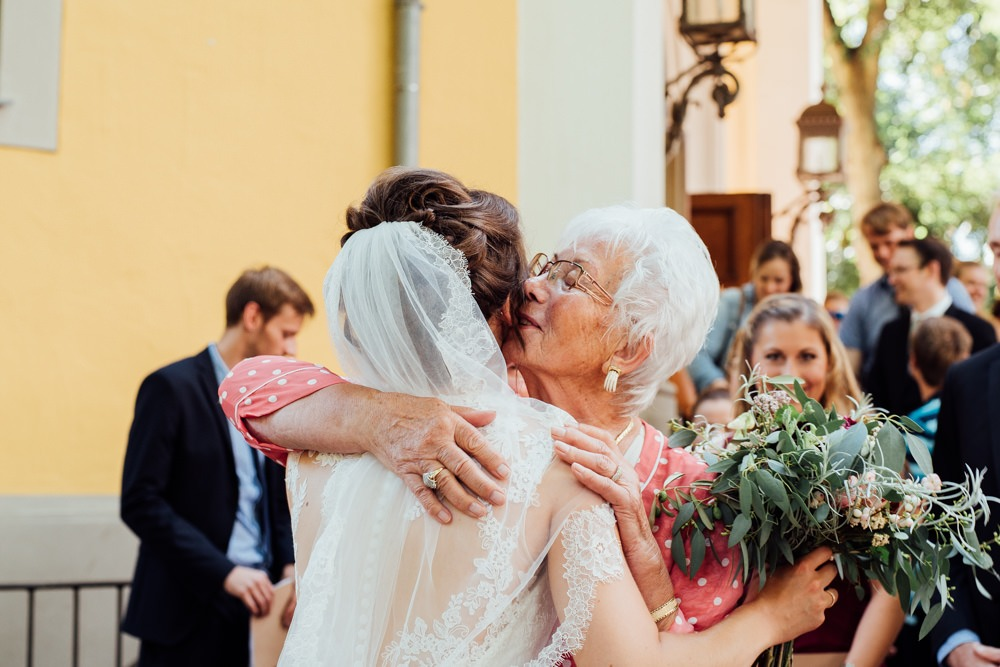 Oma / Großmutter der Braut gratuliert ihr gerührt vor der Kirche und umarmt ihr frisch verheiratetes Enkelkind herzlich.