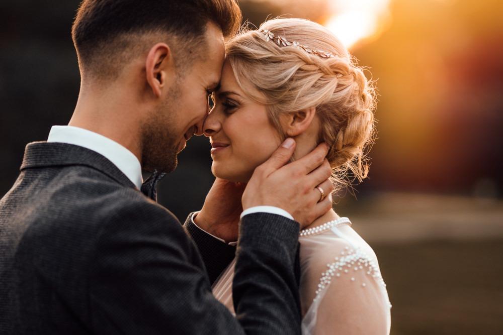 Bräutigam zieht Braut nah an sich heran. Ihre Nasen berühren sich. Im Hintergrund die perfekte Abendsonne.