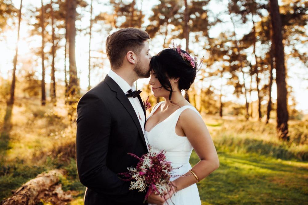 Brautpaar auf einer lichtdurchfluteten Lichtung mitten im Wald. Er küsst sie sinnlich auf die Stirn.