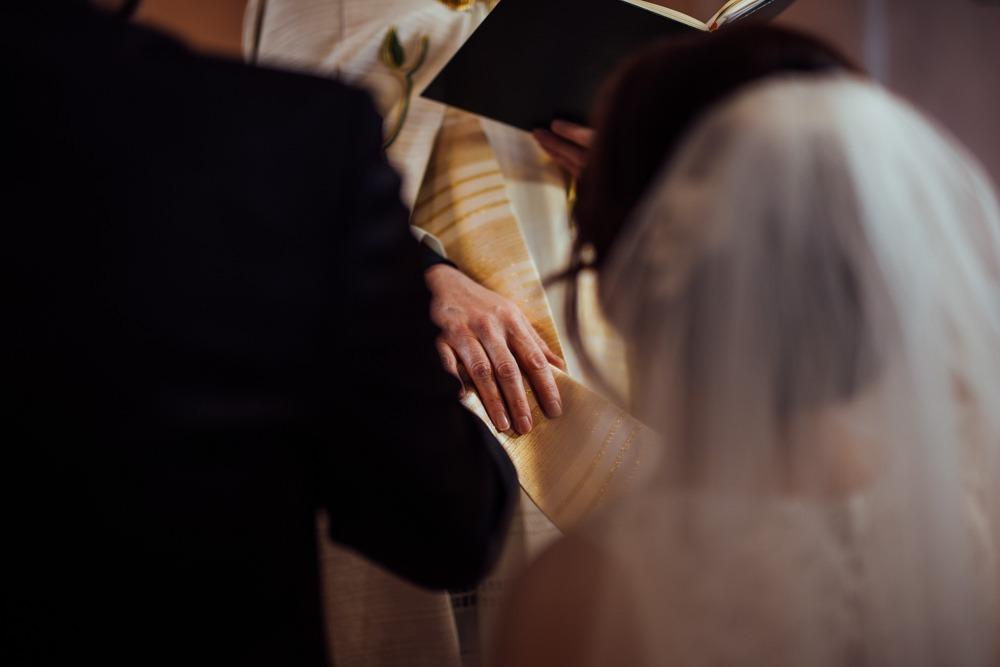 Pfarrer legt seine Hand zum Gebet / Segen auf während einer traditionellen katholischen Trauung.