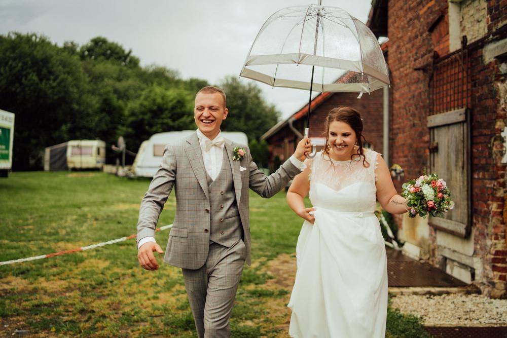 Titelbild einer Hochzeitsreportage. Brautpaar ist glücklich, trotz Regen am Hochzeitstag.