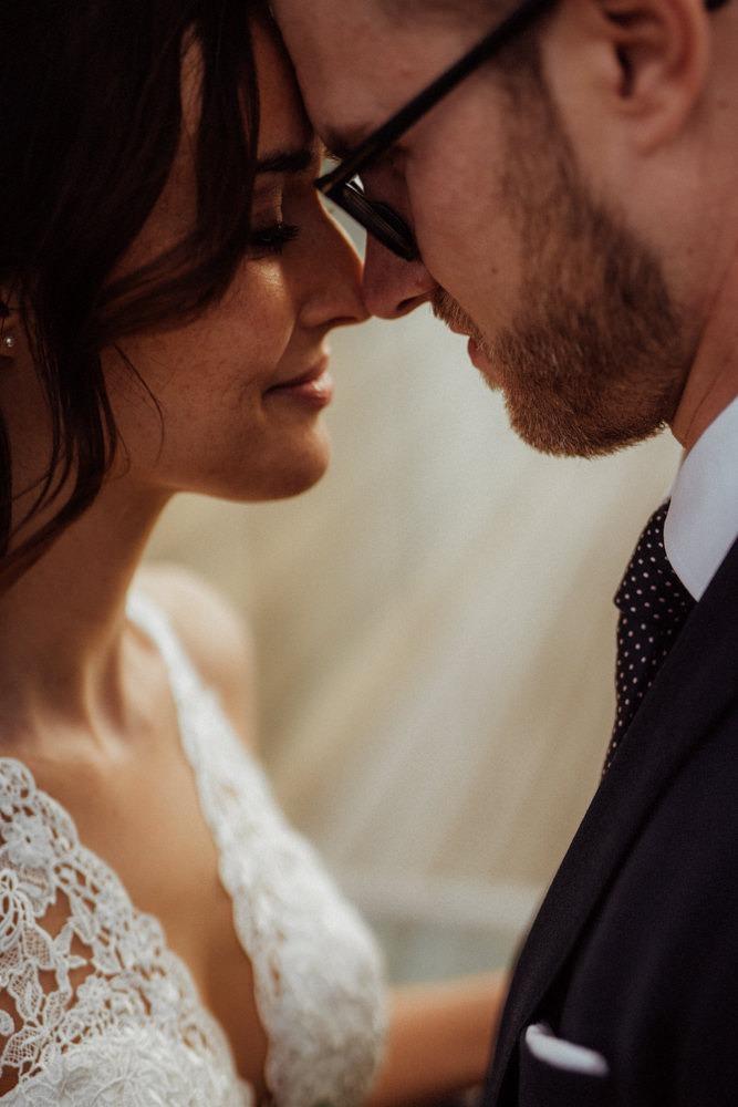 Romantische Nahaufnahme von einem Brautpaar, das sich mit den Nasen berührt.