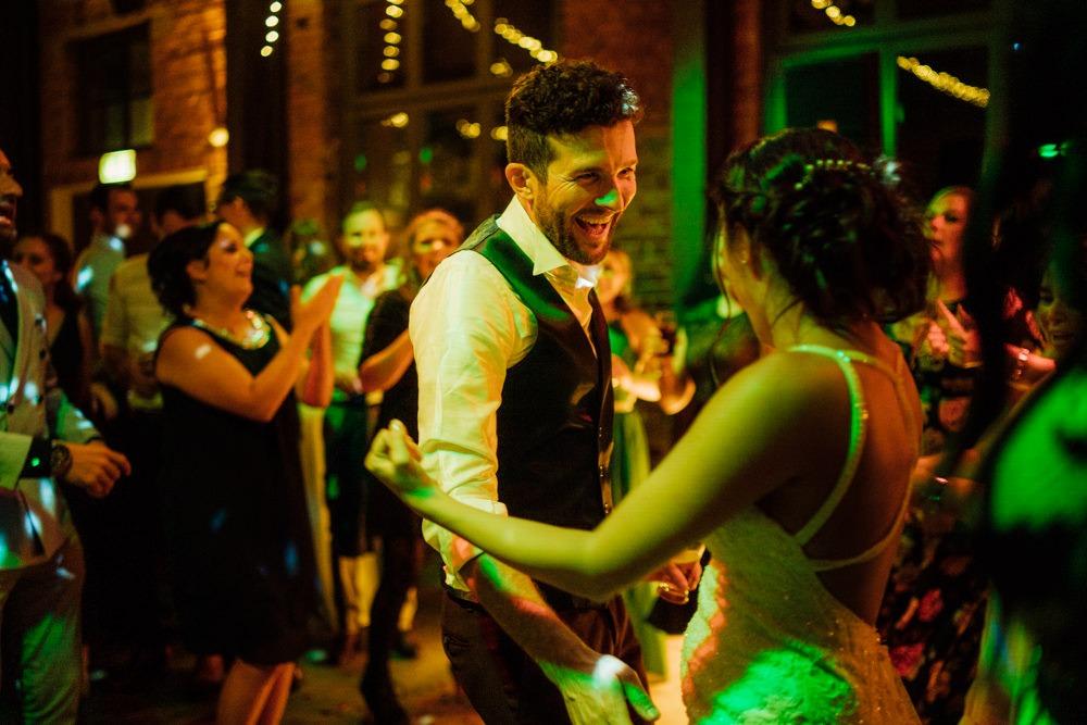 Brautpaar tanzt ausgelassen auf ihrer Hochzeitsfeier. Umgeben von ihren Freunden in buntem Partylicht.