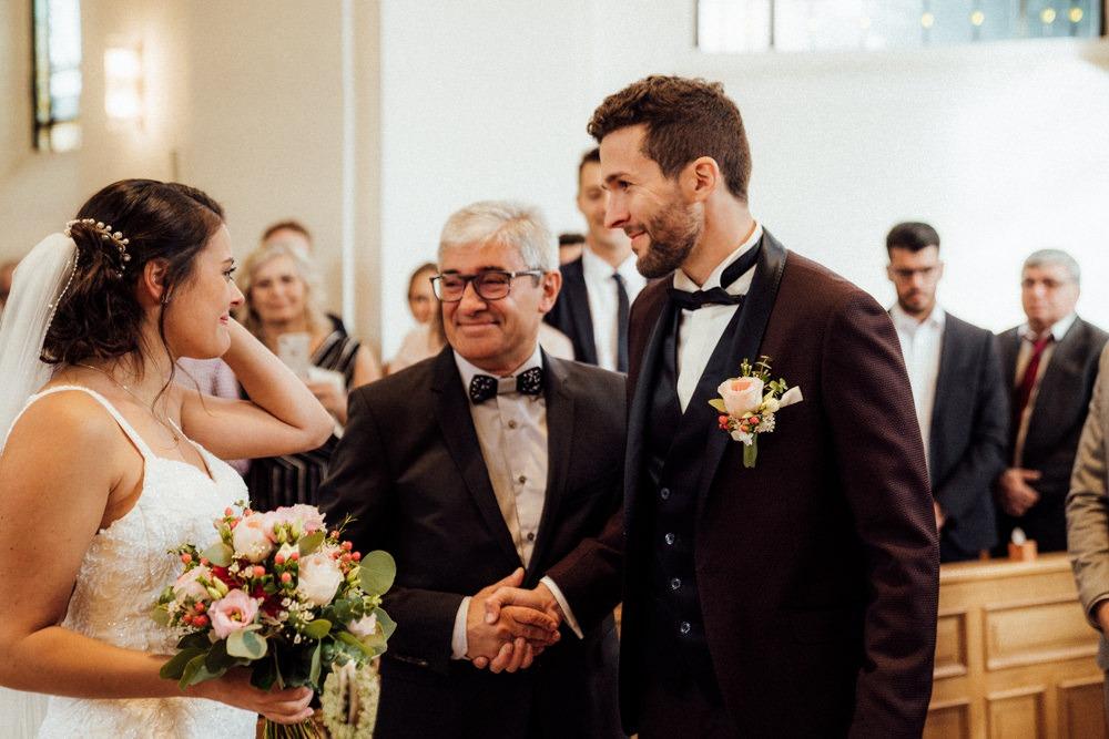 Brautvater übergibt die Braut an ihren Bräutigam in einer katholischen Kirche. Ein sehr emotionaler Moment für das junge Paar und den stolzen Vater der Braut.
