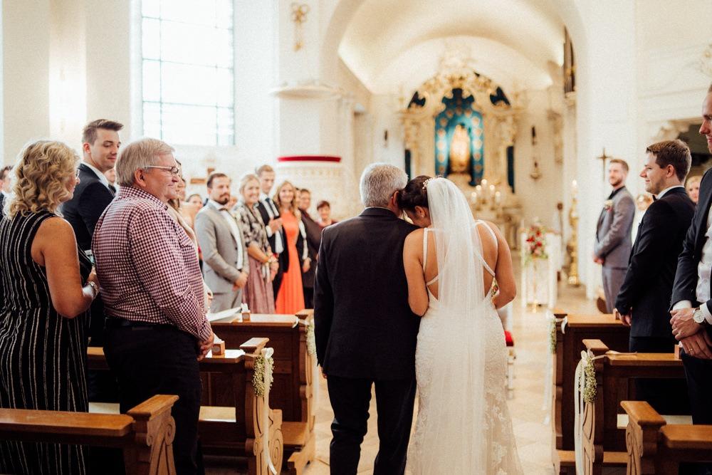 Braut schmiegt sich beim Einlauf in die Kirche noch ein letztes Mal an ihren Vater, der sie zum Altar führt.